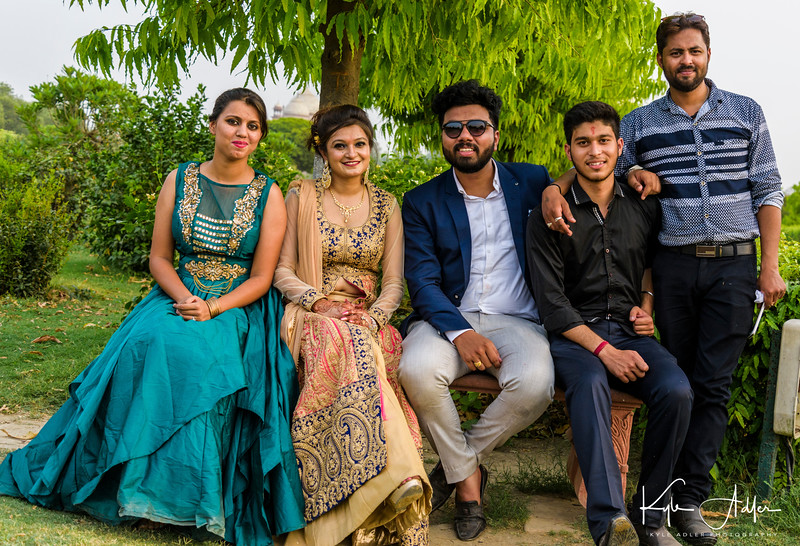 A wedding party poses for a photoshoot near the moonlight garden with a view over the river to the Taj Mahal.