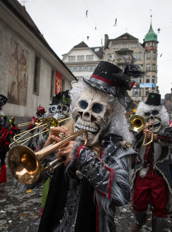 . Members of a carnival band in costumes attend the opening of the Lucerne carnival in Lucerne, Switzerland, on the so-called dirty Thursday, Feb. 27, 2014. (AP Photo/Keystone, Sigi Tischler)