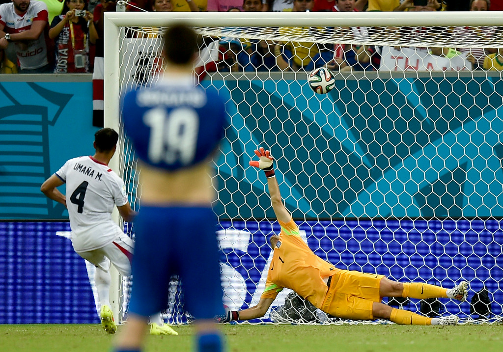 . Costa Rica\'s Michael Umana, left, scores on Greece\'s goalkeeper Orestis Karnezis during an extra time shootout giving Costa Rica a 5-3 victory in penalty shootouts after a 1-1 tie during the World Cup round of 16 soccer match between Costa Rica and Greece at the Arena Pernambuco in Recife, Brazil, Sunday, June 29, 2014. (AP Photo/Martin Meissner)