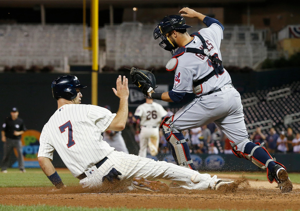 . Minnesota Twins\' Joe Mauer scores the go-ahead run as Cleveland Indians catcher Yan Gomes can\'t handle the throw to the plate on a fielder\'s choice with the bases loaded in the 11th inning of a baseball game Sunday, July 17, 2016, in Minneapolis. The Twins won 5-4. (AP Photo/Jim Mone)