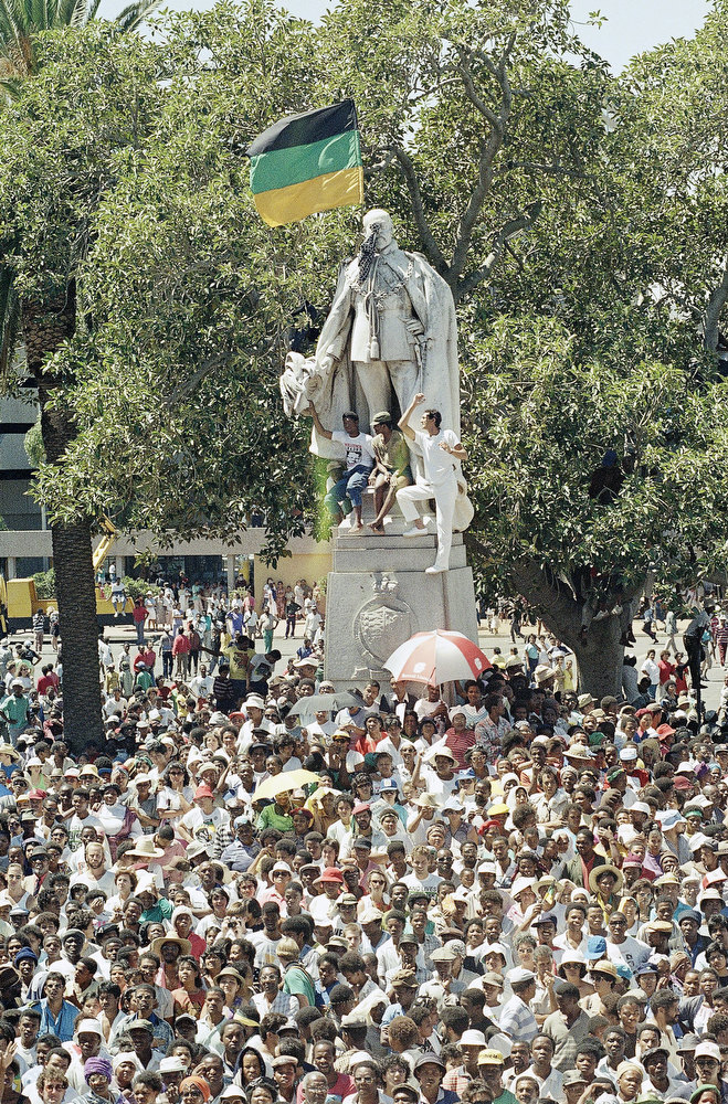 . As a supporter waves the African National Congress flag at the statue of Britainís former King Edward, thousands throng Parade Square, on Sunday, Feb. 11, 1990 in Cape Town, South Africa, awaiting the arrival of A.N.C. leader Nelson Mandela, released after his 27 years of detention. (AP Photo/Adil Bradlow)