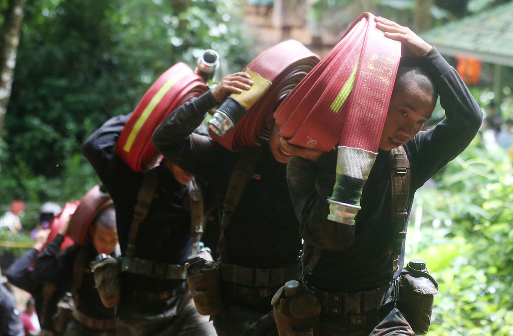 . Thai soldiers bring hoses and additional water pumps to continue the search for 12 young soccer team members and their coach after going missing in Tham Luang Nang Non cave in Mae Sai, Chiang Rai province, northern Thailand Wednesday, June 27, 2018. Rain is continuing to fall and water levels keep rising inside a cave in northern Thailand, frustrating the search for the 12 boys and their soccer coach who have been missing since Saturday. (AP Photo/Sakchai Lalit)