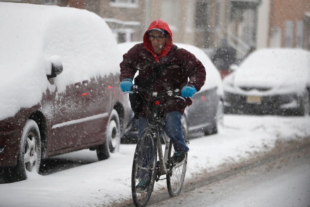 . A man rides a bicycle under a snowstorm, Saturday, Jan. 7, 2017, in Jersey City, N.J. (AP Photo/Julio Cortez)