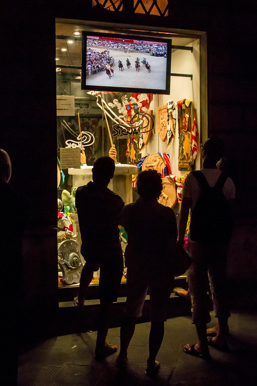 Watching a Palio video in a shop window