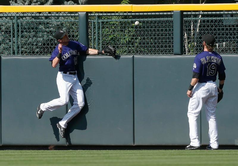 . Colorado Rockies centerfielder Drew Stubbs, left, runs into wall as right fielder Charlie Blackmon looks on as ball hit off bat of San Francisco Giants\' Hunter Pence for a three-run home run falls in the bullpen in the first inning of a baseball game in Denver on Monday, Sept. 1, 2014. (AP Photo/David Zalubowski)