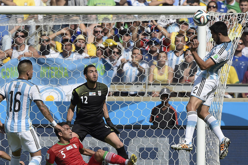 . Iran\'s goalkeeper Alireza Haqiqi (C) defends as Argentina\'s defender Ezequiel Garay (R) makes an attempt on goal during the Group F football match between Argentina and Iran at the Mineirao Stadium in Belo Horizonte during the 2014 FIFA World Cup in Brazil on June 21, 2014.  (JUAN MABROMATA/AFP/Getty Images)