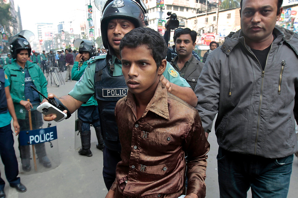 Description of . Bangladeshi policemen detain an opposition activist, center, in front of the main opposition Bangladesh Nationalist party office during a nationwide half-day strike in Dhaka, Bangladesh, on Thursday, Dec. 13, 2012. Homemade bombs exploded in Bangladesh's capital and police fired tear gas at demonstrators as opposition parties enforced a general strike on Thursday, demanding that the government restore an election-time caretaker administration. (AP Photo/A.M. Ahad)
