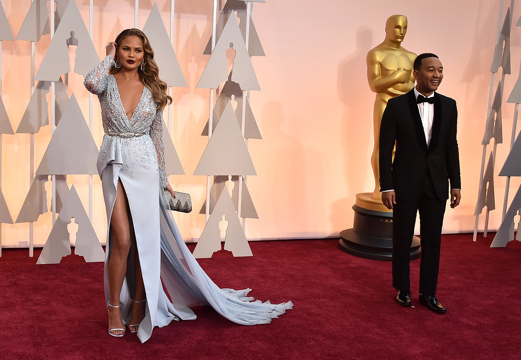 . Chrissy Teigen, left, and John Legend arrive at the Oscars on Sunday, Feb. 22, 2015, at the Dolby Theatre in Los Angeles. (Photo by Jordan Strauss/Invision/AP)