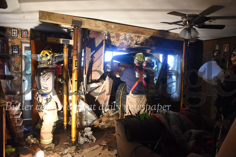 Harold Aughton/Butler Eagle: Emergency workers assess the damage sustained to a home at 1204 Herman Road in Clearfield Twp after the driver of a Jeep Wrangler lost control.