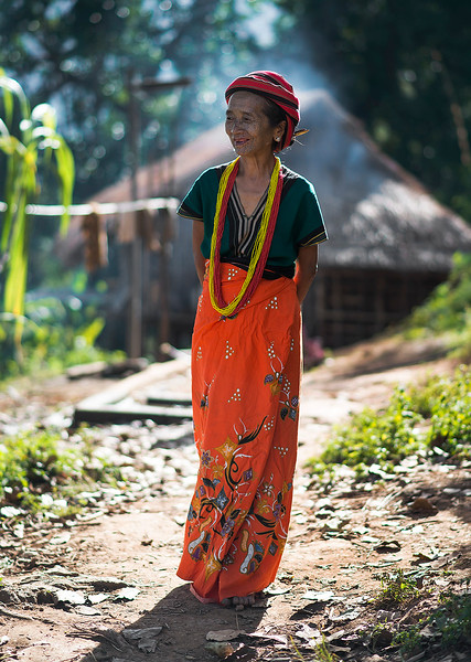A tribal woman with face tattoos outside her home.  Chin State, Myanmar, 2017.