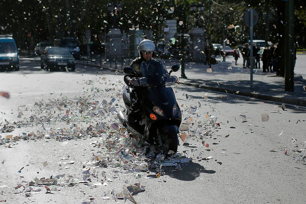 . A man drives his motorcycle as papers fly around during the first day of a garbage collectors strike in Madrid, Tuesday, Nov. 5, 2013. Street cleaners and garbage collectors who work in the city\'s public parks walked off the job at midnight in a strike called by trade unions to contest the planned layoff of more than 1,000 workers. Madrid\'s municipal cleaning companies, which have service supply contracts with the city authorities, employ some 6,000 staff. (AP Photo/Andres Kudacki)