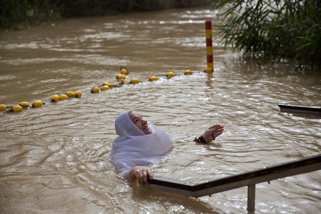 . A Christian Orthodox pilgrim swims after she was baptized during the traditional Epiphany baptism ceremony at the Qasr-el Yahud baptism site in the Jordan river near the West Bank town of Jericho, Monday, Jan. 18, 2016. The site is traditionally believed by many to be the place where Jesus was baptized.  (AP Photo/Ariel Schalit)