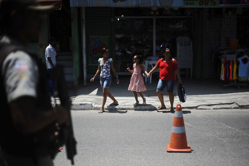 . A policeman patrols as a family crosses a street in the Nordeste de Amaralina slum complex in Salvador, Bahia State, March 28, 2013. One of Brazil\'s main tourist destinations and a 2014 World Cup host city, Salvador suffers from an unprecedented wave of violence with an increase of over 250% in the murder rate, according to the Brazilian Center for Latin American Studies (CEBELA). Picture taken March 28, 2013.  REUTERS/Lunae Parracho