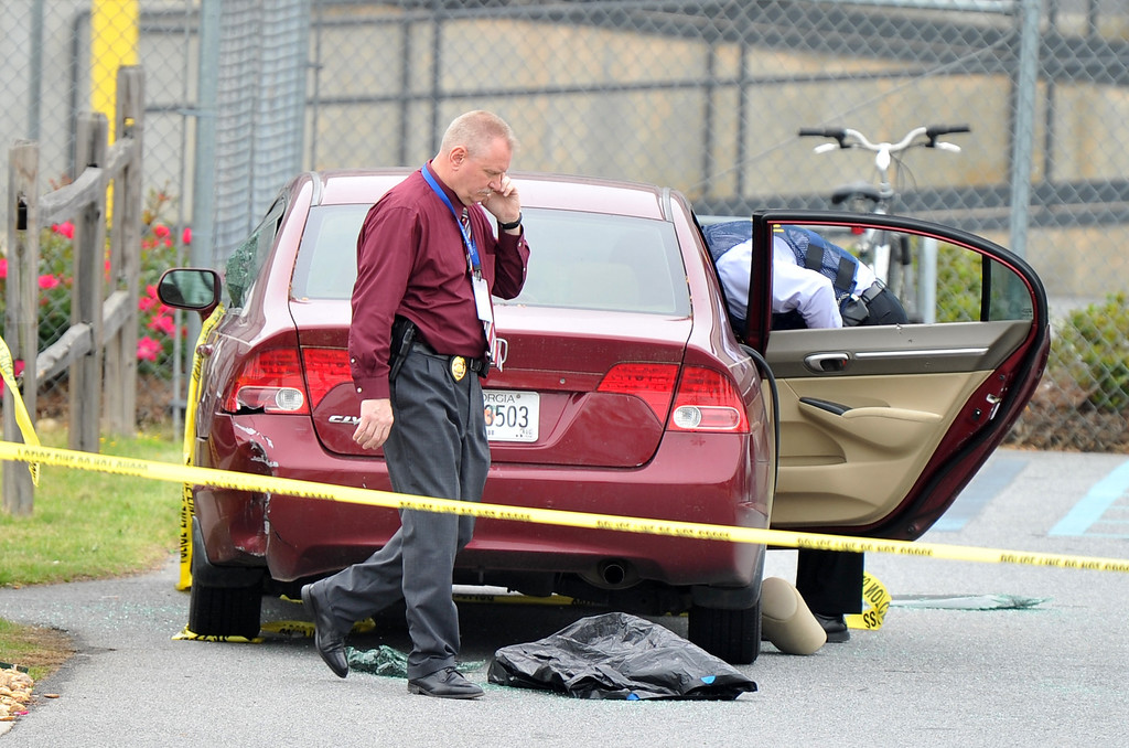 . Police officials search a car located at the scene of the shooting that took place at a FedEx facility in Kennesaw, Ga., on Tuesday, April 29, 2014.  (AP Photo/Atlanta Journal-Constitution, Brant Sanderlin)
