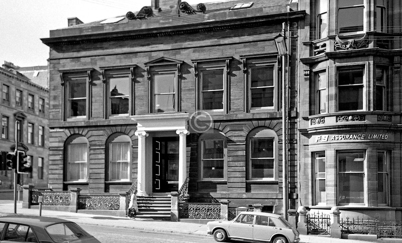 West George St, north side east of Wellington St.  This lovely late Georgian house (probably by John Brash, who built Blythswood Square) has had  its windows restored to their original form, divided by astragals into small panes,  which is a great improvement on the wall-eyed look it has here.  