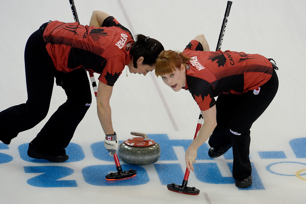 . Canadian curlers Jill Officer (left) and Dawn McEwen sweep the ice ahead of the stone during a women\'s curling qualifier against Great Britain at the Ice Cube Curling Center. Sochi 2014 Winter Olympics on Wednesday, February 12, 2014. (Photo by AAron Ontiveroz/The Denver Post)