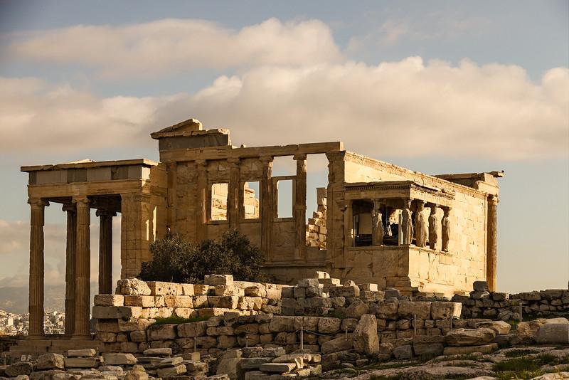 Golden sunlight illuminates the ruins of the Acropolis.