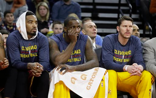 . From left, Cleveland Cavaliers guard J.R. Smith, center Kendrick Perkins and guard Mike Miller watch during the first half of an NBA basketball game against the Detroit Pistons, Tuesday, Feb. 24, 2015 in Auburn Hills, Mich. Perkins was acquired from the Oklahoma City Thunder. (AP Photo/Carlos Osorio)