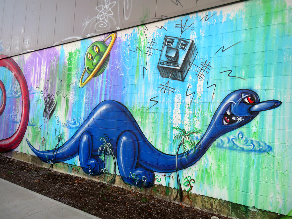kenny scharf mural on the side of Krinos food - dinosaur