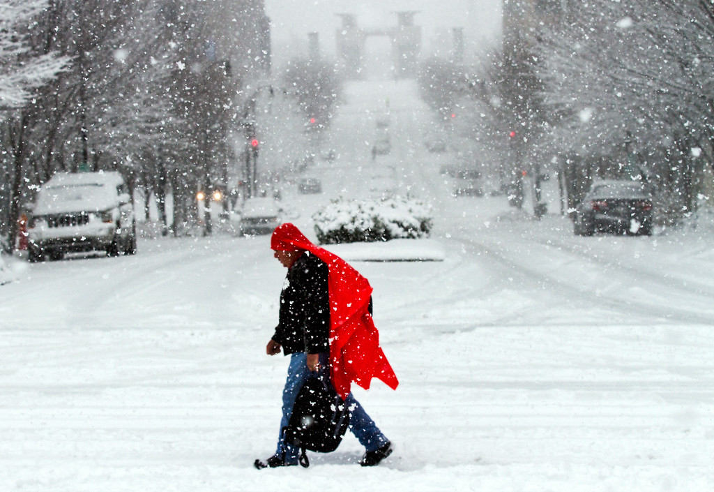 . A man walks through heavy snow in downtown Nashville, Tenn., on Friday, Jan. 22, 2016. Much of downtown was deserted as state and city government offices were closed for the day. (AP Photo/Erik Schelzig)
