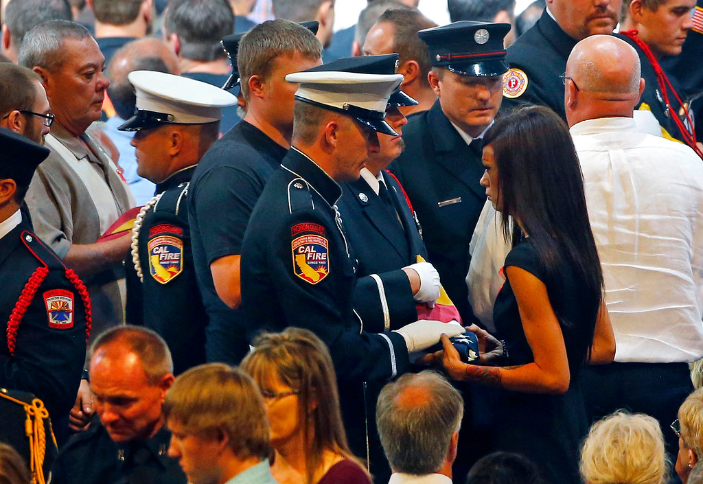 . An honor guard presents Juliann Ashcraft, wife of fallen firefighter Andrew Ashcraft, with an American flag during a memorial service at Tim\'s Toyota Center in Prescott Valley, Ariz.,  Tuesday, July 9, 2013, for the 19 Granite Mountain hotshot firefighters that were killed on June 30 while battling the Yarnell Hill Fire. (AP Photo/The Arizona Republic, David Kadlubowski, Pool)