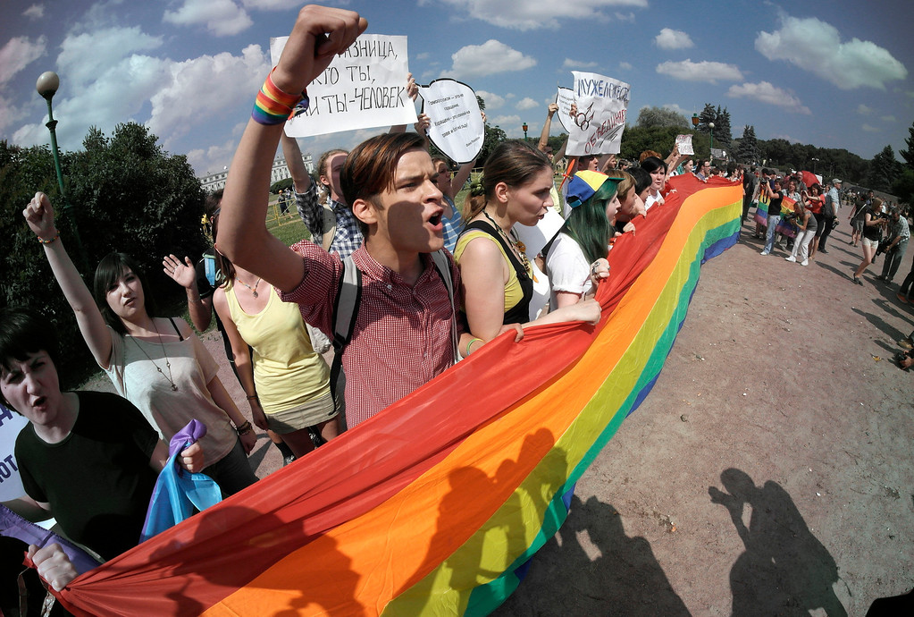 . Gay rights activists shout slogans during their authorized rally in St.Petersburg, Russia, Saturday, June 29, 2013.  Police detained several gay activists, who were outnumbered by the protesters. Dozens of gay activists had to be protected by police as they gathered for the parade, which proceeded with official approval despite recently passed legislation targeting gays. (AP Photo/Dmitry Lovetsky)