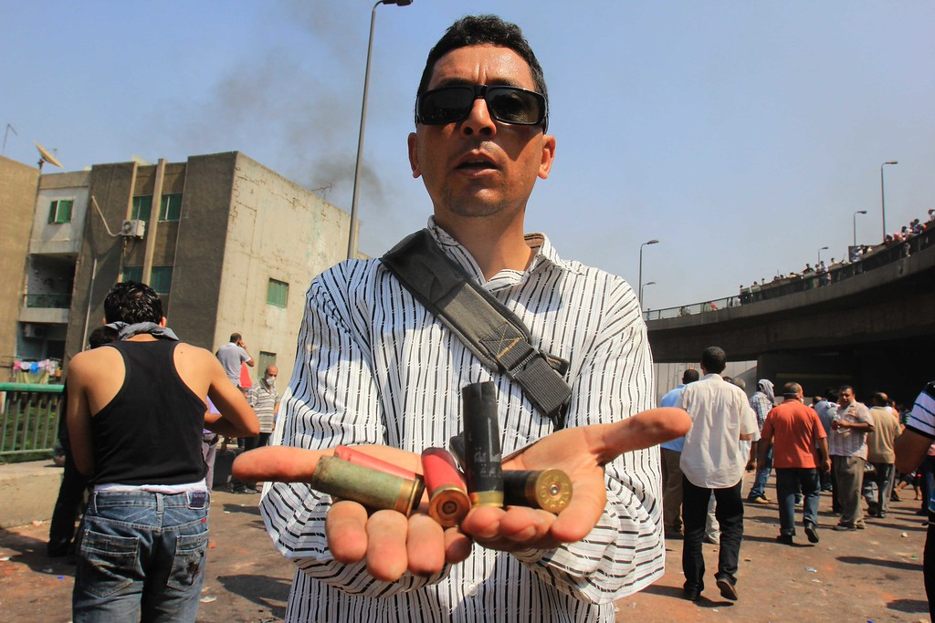 . A supporters of Egypt\'s ousted President Mohammed Morsi shows spent ammunition during clashes with security forces near the largest sit-in by supporters of ousted Islamist President Mohammed Morsi in the eastern Nasr City district of Cairo, Egypt, Wednesday, Aug. 14, 2013.   (AP Photo/Mohammed Abu Zeid)
