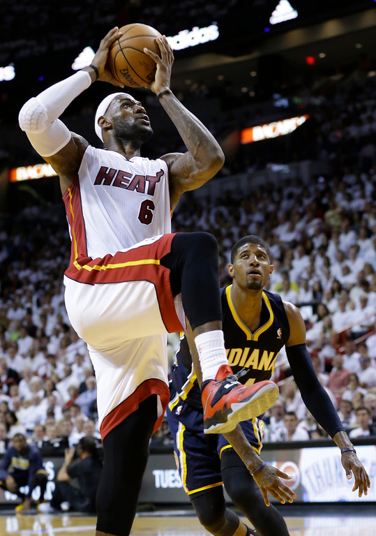 . Miami Heat forward LeBron James (6) aims to dunk the ball over Indiana Pacers forward Paul George (24), during the second half of Game 4 in the NBA basketball Eastern Conference finals playoff series, Monday, May 26, 2014, in Miami. (AP Photo/Wilfredo Lee)