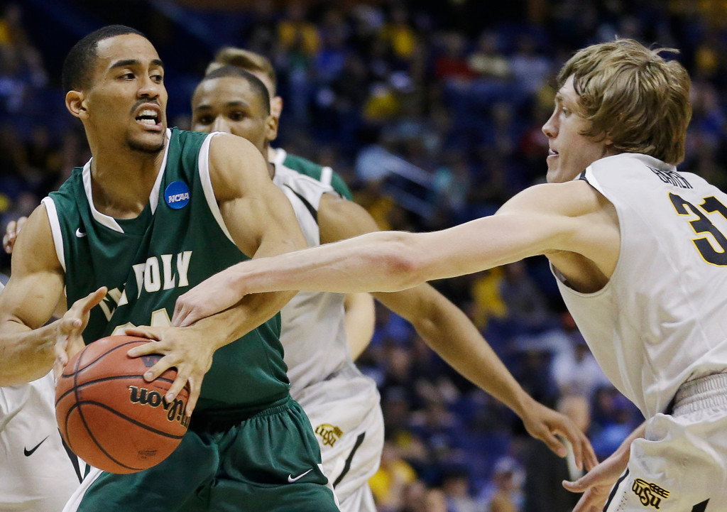 . Wichita State guard Ron Baker (31) goes after the ball against Cal Poly guard Jamal Johnson (24) during the first half of a second-round game in the NCAA college basketball tournament Friday, March 21, 2014, in St. Louis. (AP Photo/Jeff Roberson)