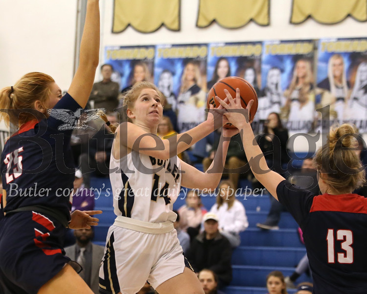 Butler's Macklin Hanley (14) drives for a shot against Shaler's Meghan Lacey (13) and Claire Grunden (25) in Monday night's 49-42 home win. Seb Foltz/Butler Eagle