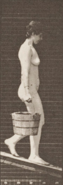 Nude woman descending an incline with a bucket of water