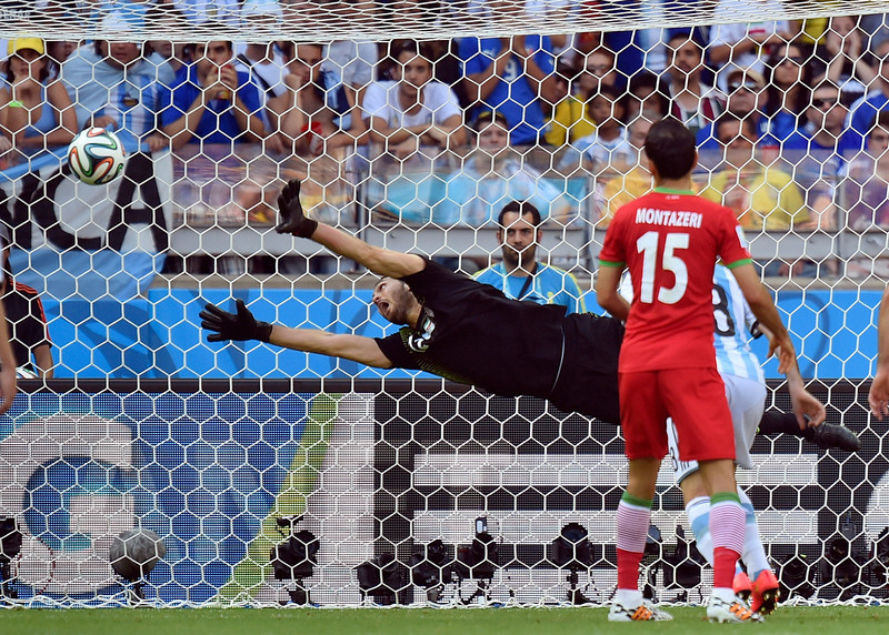 . Iran\'s goalkeeper Alireza Haghighi dives but fails to stop a goal by Argentina\'s Lionel Messi during the group F World Cup soccer match between Argentina and Iran at the Mineirao Stadium in Belo Horizonte, Brazil, Saturday, June 21, 2014. Argentina defeated Iran 1-0. (AP Photo/Martin Meissner)