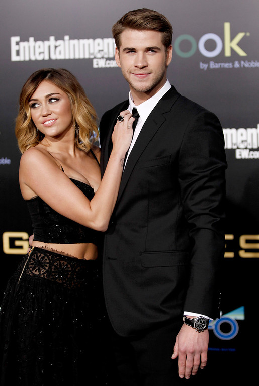 """. Liam Hemsworth, right, and Miley Cyrus arrive at the world premiere of \""""The Hunger Games\"""" on Monday March 12, 2012 in Los Angeles. (AP Photo/Matt Sayles)"""