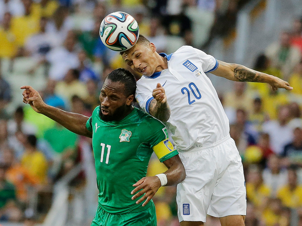 . Greece\'s Jose Holebas heads the ball over Ivory Coast\'s Didier Drogba during the group C World Cup soccer match between Greece and Ivory Coast at the Arena Castelao in Fortaleza, Brazil, Tuesday, June 24, 2014. (AP Photo/Bernat Armangue)