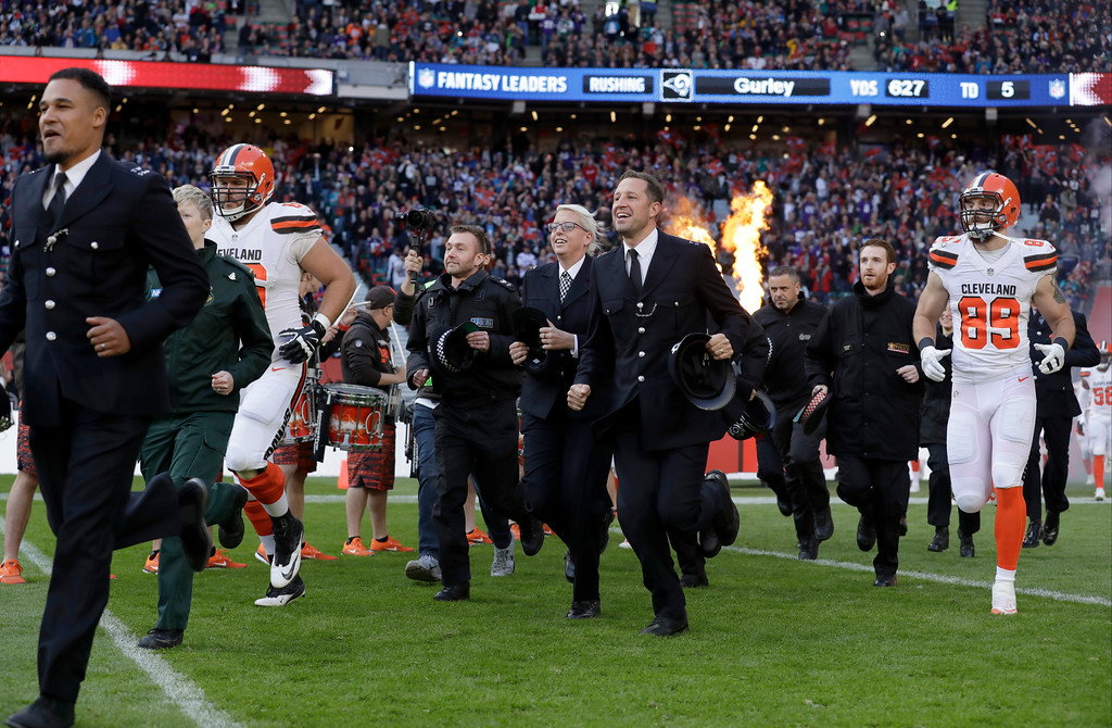 . Members of Britain\'s emergency services join Cleveland Browns players as they run onto the field before an NFL football game between the Cleveland Browns and the Minnesota Vikings at Twickenham Stadium in London, Sunday Oct. 29, 2017. (AP Photo/Matt Dunham)