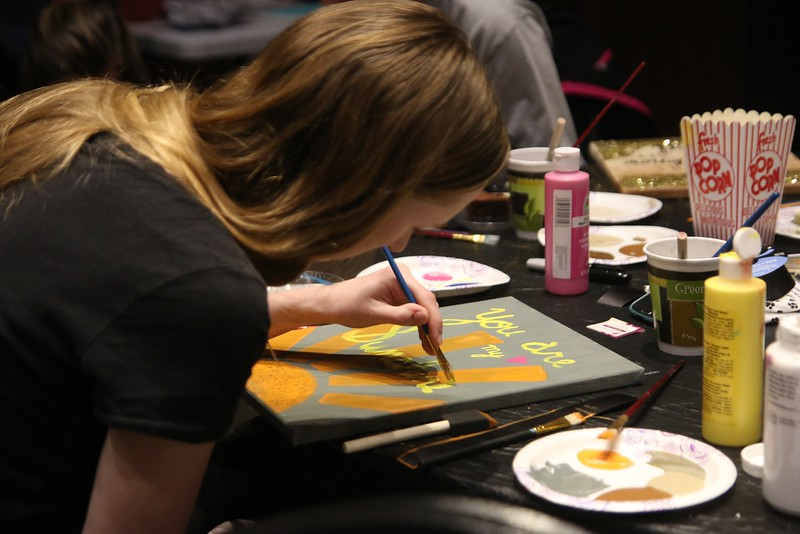 "Senior, Lydia Hill, painted a canvas including the quote ""you are my sunshine."""