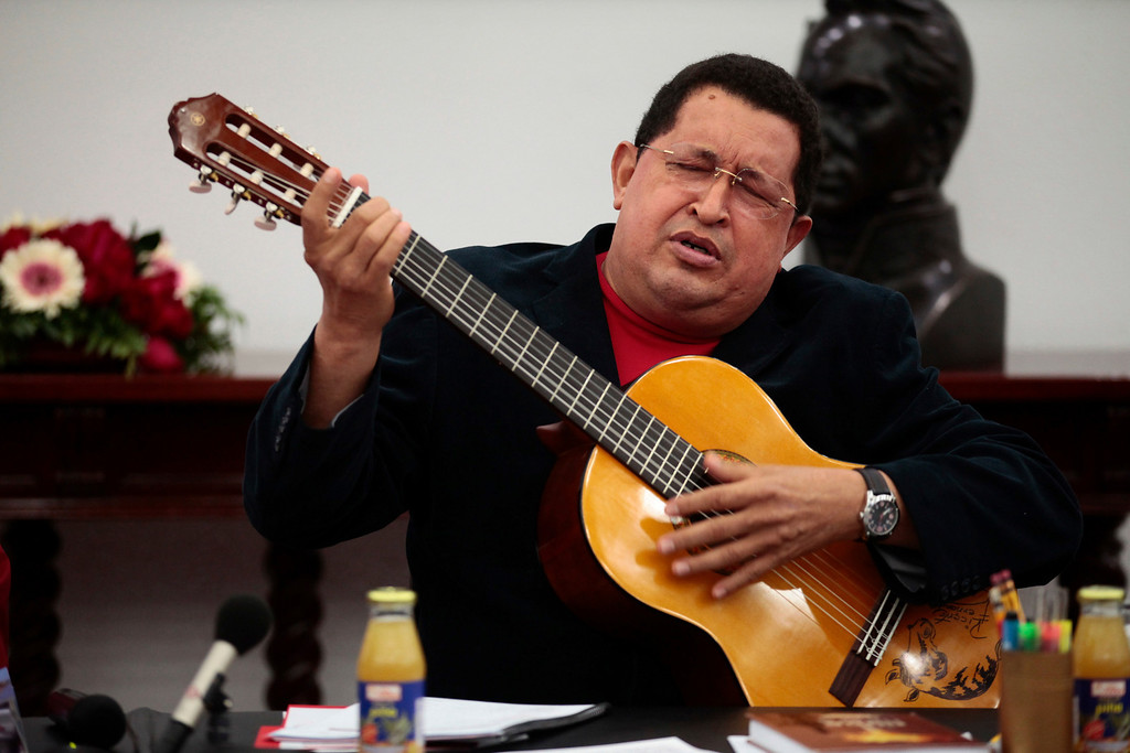 . Venezuelan President Hugo Chavez plays a guitar, which was a gift from Mexican singer Vicente Fernandez, during a cabinet meeting at Miraflores Palace in Caracas September 20, 2012. Venezuelans will go to the polls for the presidential election on October 7. REUTERS/Miraflores Palace
