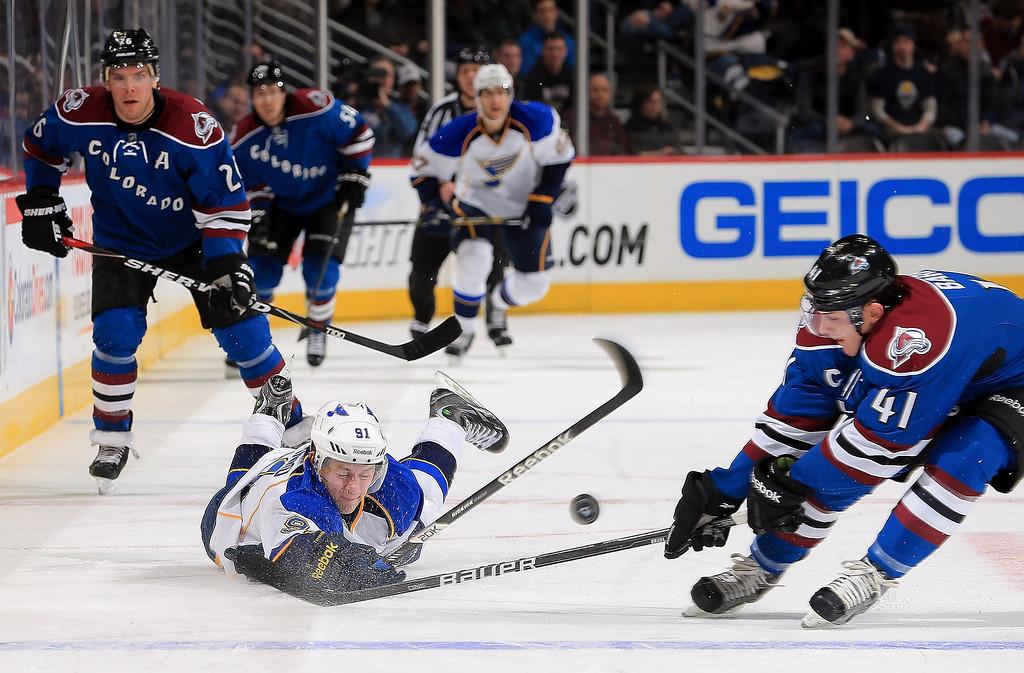 . Vladimir Tarasenko #91 of the St. Louis Blues dives to move the puck over the blue line against Tyson Barrie #41 of the Colorado Avalanche at the Pepsi Center on February 20, 2013 in Denver, Colorado.  (Photo by Doug Pensinger/Getty Images)