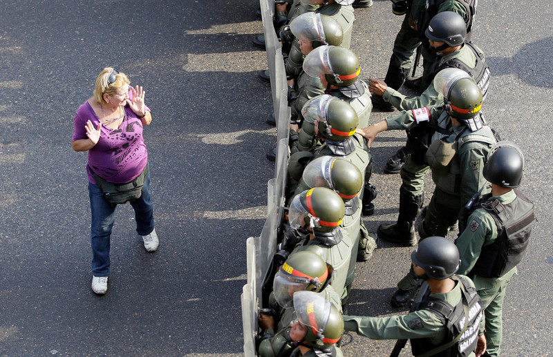 . An opposition supporter walks by a line of riot police along a highway in the Altamira neighborhood of Caracas, Venezuela, Monday, April 15, 2013. The opposition is protesting the official results in Venezuela\'s disputed Sunday presidential election. Opposition candidate Henrique Capriles has challenged his narrow loss to Nicolas Maduro and is demanding a recount.  (AP Photo/Fernando Llano)