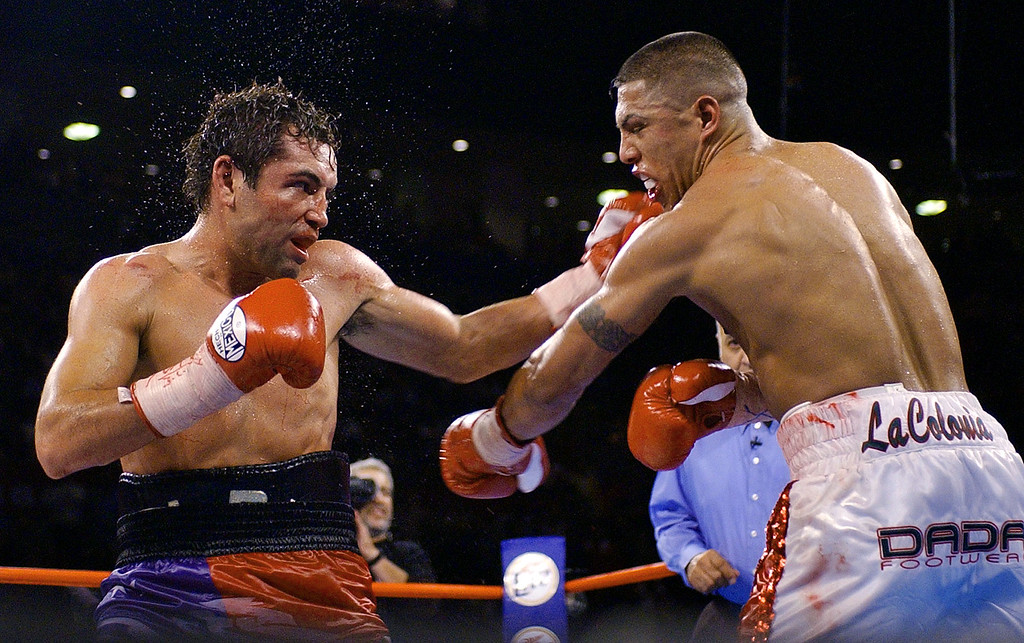 . Oscar De La Hoya, left, lands a left that knocks down Fernando Vargas in the 11th round  of their 154-pound championship bout at the Mandalay Bay Resort & Casino in Las Vegas, Saturday, Sept. 14, 2002. De La Hoya won the bout by TKO. (AP Photo/Laura Rauch)
