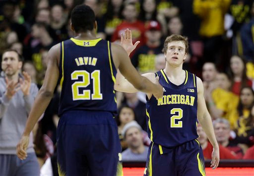 . Michigan guard Spike Albrecht, right, high-fives teammate Zak Irvin in the second half of an NCAA college basketball game against Maryland, Saturday, Feb. 28, 2015, in College Park, Md. (AP Photo/Patrick Semansky)
