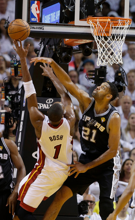 . San Antonio Spurs forward Tim Duncan (21) blocks a shot to the basket by Miami Heat center Chris Bosh (1), during the first half in Game 4 of the NBA basketball finals, Thursday, June 12, 2014, in Miami.  (AP Photo/Lynne Sladky)