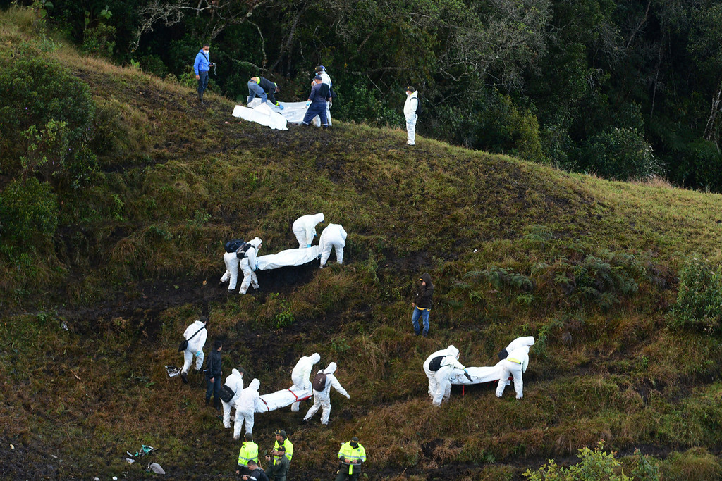 . Rescue workers carry the bodies of victims of an airplane that crashed in a mountainous area outside Medellin, Colombia, Tuesday, Nov. 29, 2016. The plane was carrying the Brazilian first division soccer club Chapecoense team that was on it\'s way for a Copa Sudamericana final match against Colombia\'s Atletico Nacional. (AP Photo/Luis Benavides)
