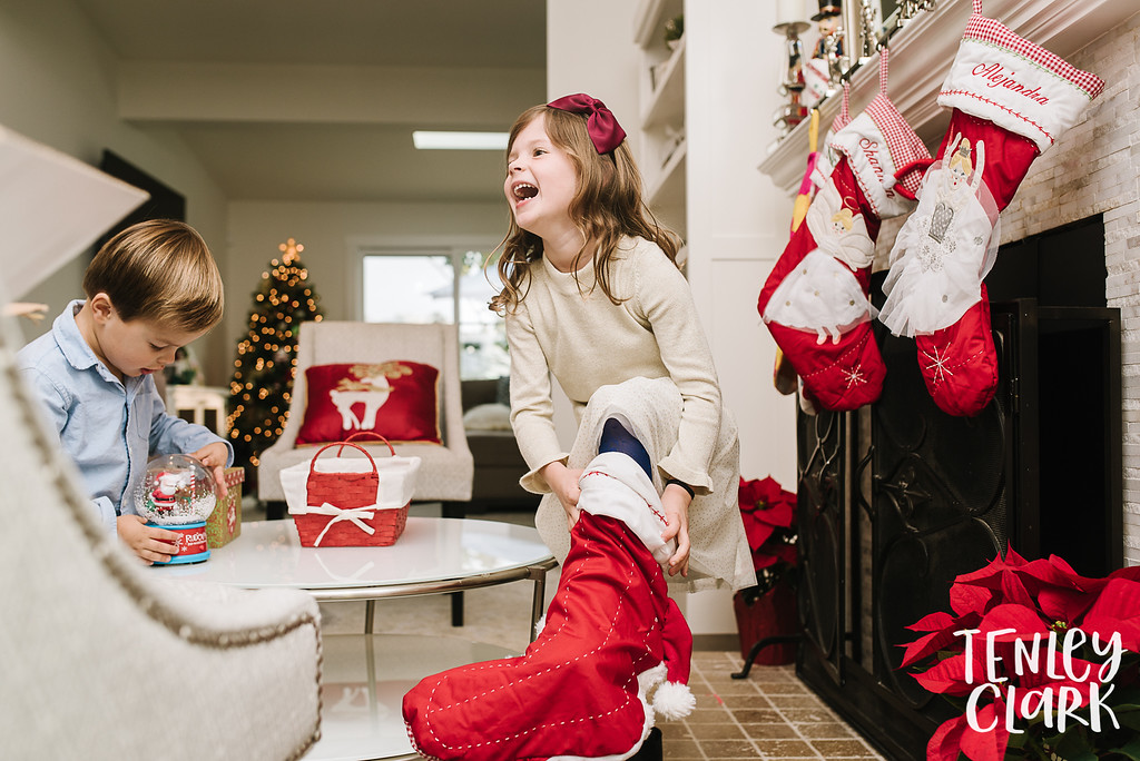 Little girl wearing Christmas stocking as sock. Lifestyle in-home family photoshoot in Marin, CA by Tenley Clark Photography.