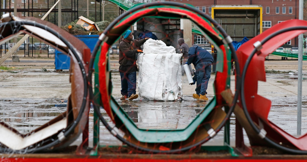 . Workers are seen through the tree netting rings as they brave the brisk wind and cold temperatures, to wrap up one of the five 60x100 ft. tent sections that made up the Jackson Giant Tree Company on the Mississippi State Fairgrounds in Jackson, Miss., Wednesday, Dec. 27, 2017. A crew of six employees erected the Christmas tree emporium before Thanksgiving, manned the operation and then took down the facility after Christmas. (AP Photo/Rogelio V. Solis)