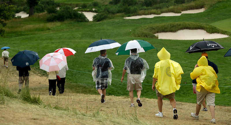 . Spectators walk off the course as a weather warning delays the first round of the U.S. Open golf tournament at Merion Golf Club, Thursday, June 13, 2013, in Ardmore, Pa. (AP Photo/Gene J. Puskar)