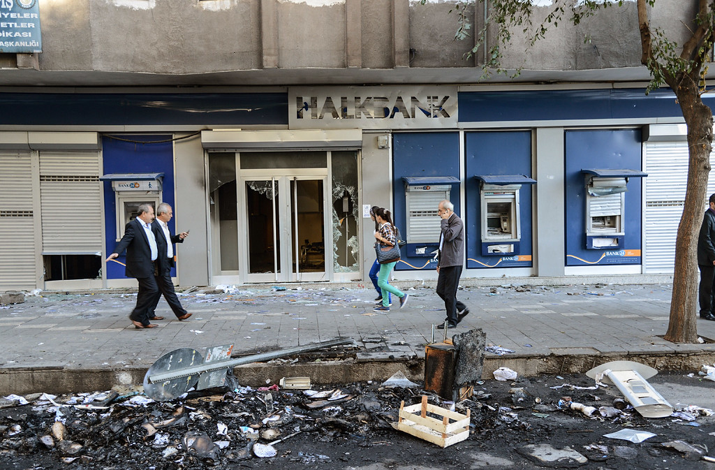 . Residents walk through a damaged street in downtown Diyarbakir on October 8, 2014, following overnight clashes with police that caused extensive damage in the city with shop fronts burned-out and buses set on fire. The Turkish army has deployed in the streets of Diyarbakir to impose a curfew, following violent protests by pro-Kurdish demonstrators in southeast Turkey angry at the government\'s lack of action against jihadists in Syria, officials said on October 8, 2014. At least 14 people were killed, 8 of the deaths came in Turkey\'s main Kurdish city of Diyarbakir where the most intense rioting took place overnight. AFP PHOTO/ILYAS AKENGINILYAS AKENGIN/AFP/Getty Images