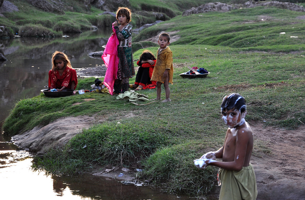 . Children, who are displaced from Pakistani tribal area due to security forces\'  operation against militants in tribal areas, wash their linens and bath in polluted stream, living under a poverty line in suburbs of Islamabad, Pakistan, Friday, Oct 17, 2014. (AP Photo/B.K. Bangash)