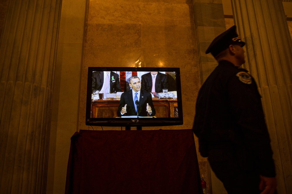 Description of . U.S. President Barack Obama is seen on a television screen in a hallway in the U.S. Capitol as he delivers his State of the Union Address February 12, 2013 in Washington, D.C. Facing a divided Congress, Obama focused his speech on new initiatives designed to stimulate the U.S. economy. (Photo by Drew Angerer-Pool/Getty Images)