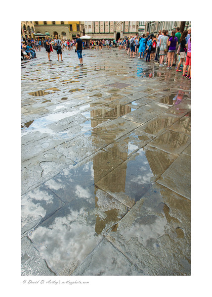 Reflection in rainwater on pavement, Duomo Bell Tower, Florence, Italy